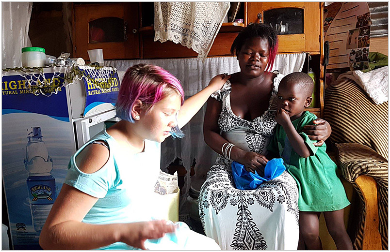 Lexi praying with a woman and her child
