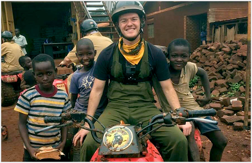 Austin on a quad bike surrounded by kids.