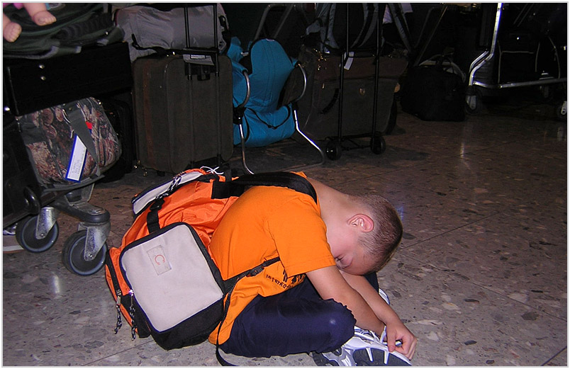 Austin asleep on the London Heathrow airport floor