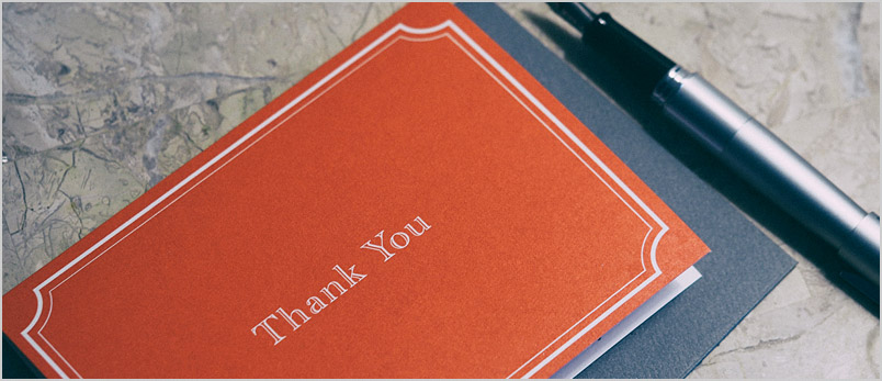 a photo of a thank-you note and pen lying on a marble top table