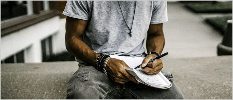Photo of a young man handwriting a note