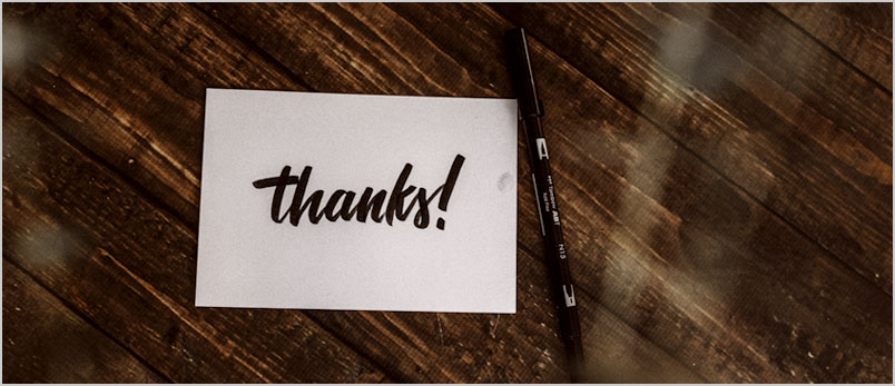 Photo of a thank you note and a pen on a wooden table