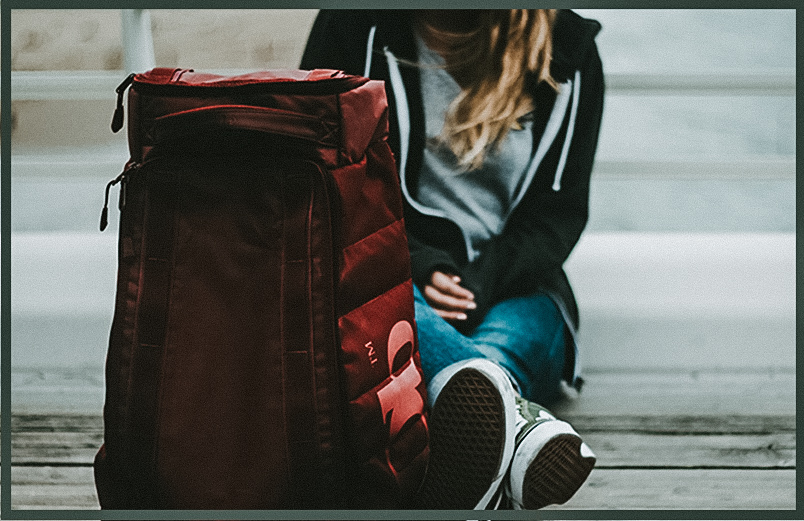 A photo of a woman sitting next to a travel bag.