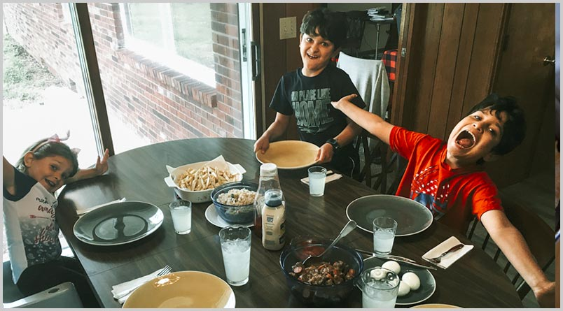A photo of Jayden, Edson, and Hadasa Tejeda around the dinner table
