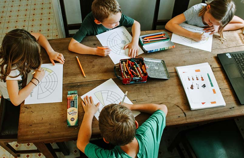Four children coloring orchestra seating charts for music class.