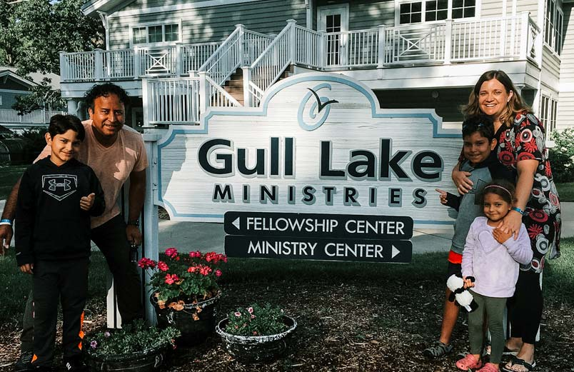 A Gerson, Betsy, and their children standing next to a sign for Gull Lake Ministries