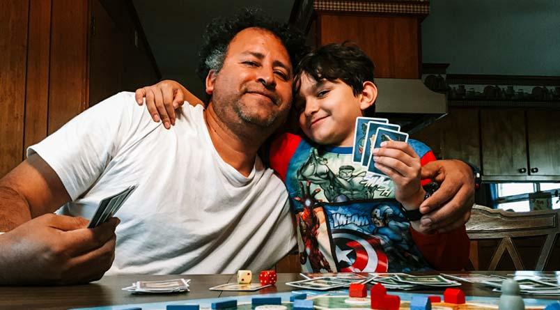 A photo of Gerson with his arm around his younger son while they play a board game