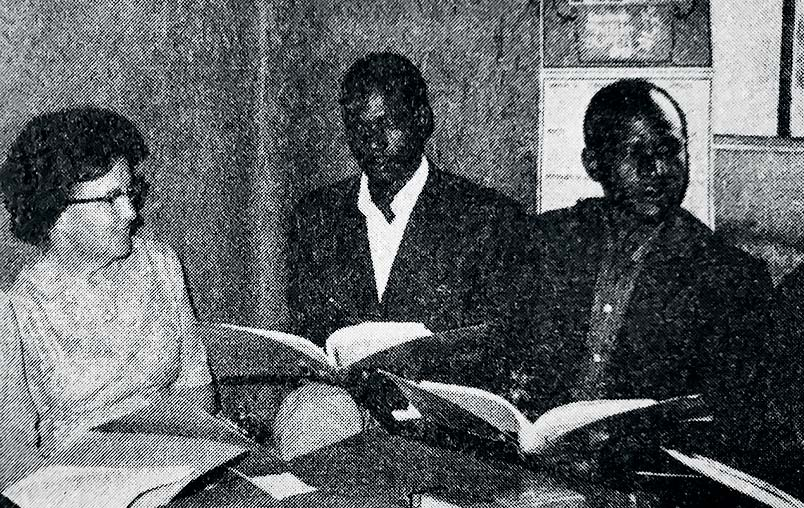 A photo of Lillie Mae Ammerman with two students in a classroom.