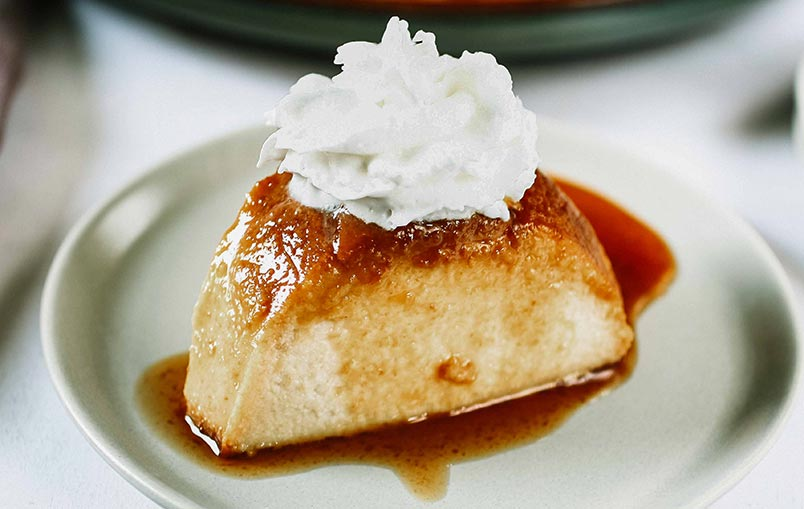 A photo of a slice of Paraguayan Bread Pudding with whipped cream on top