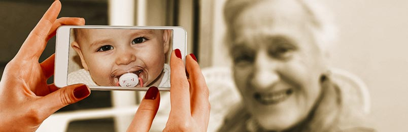 a photo of a smiling elderly woman facing a woman who is holding a phone with a photo of a baby on the screen.