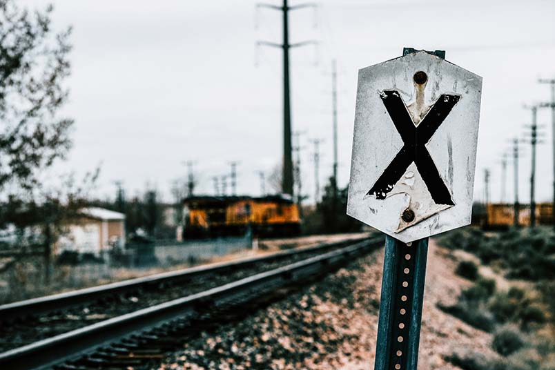 A photo of railroad tracks stretching into the distance with an X on a sign indicating
