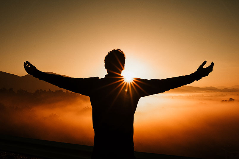 A photo of a man with arms outstretched facing a sunrise.