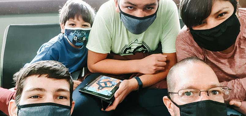 A family wearing masks in an airport waiting area