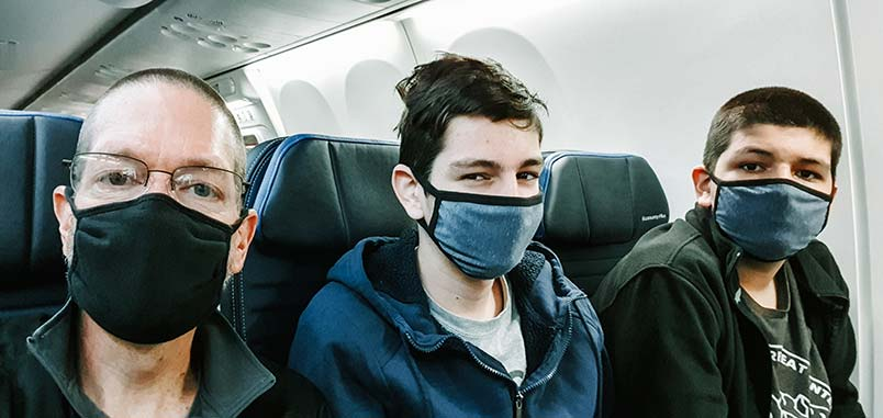 A man and his two teens, wearing masks, sitting on an airplanw