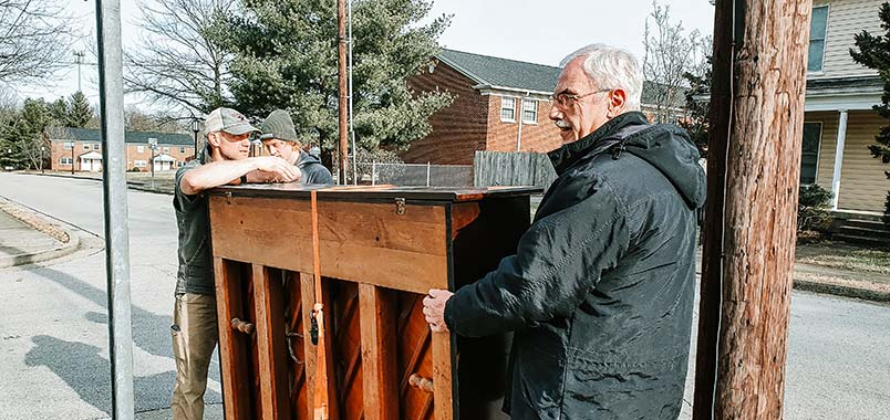 Two men moving a piano