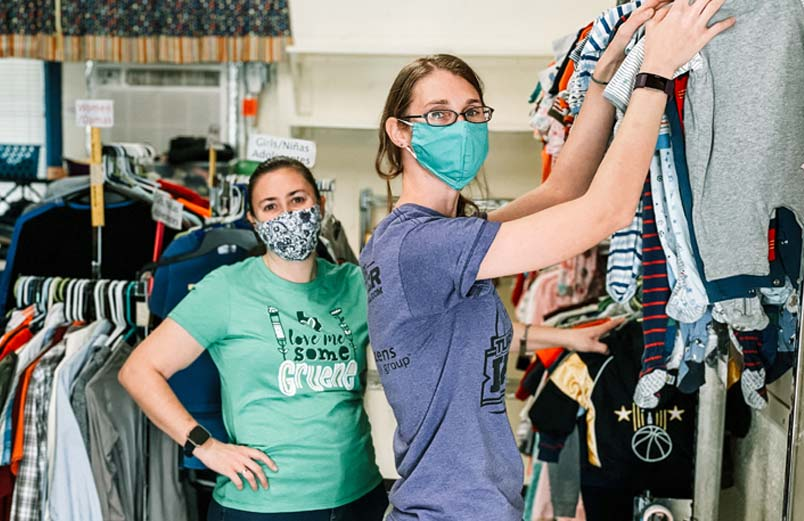 Two women wearing masks hang clothes in a store