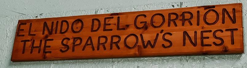 A wooden sign that says The Sparrows Nest in both Spanish and English